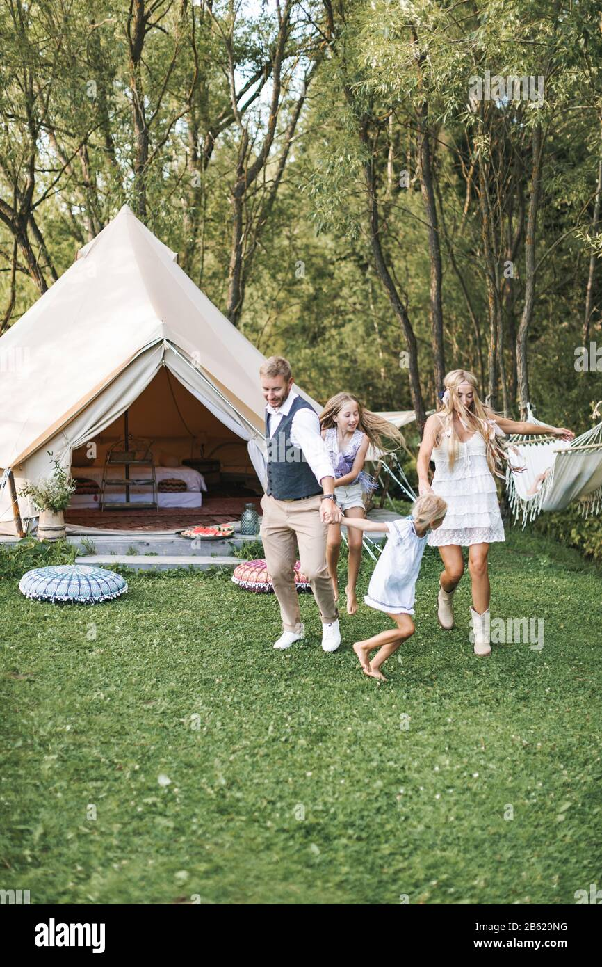 Happy family: mother, father, two children daughters on nature, dancing and running together. Cheerful family in boho light clothes Stock Photo