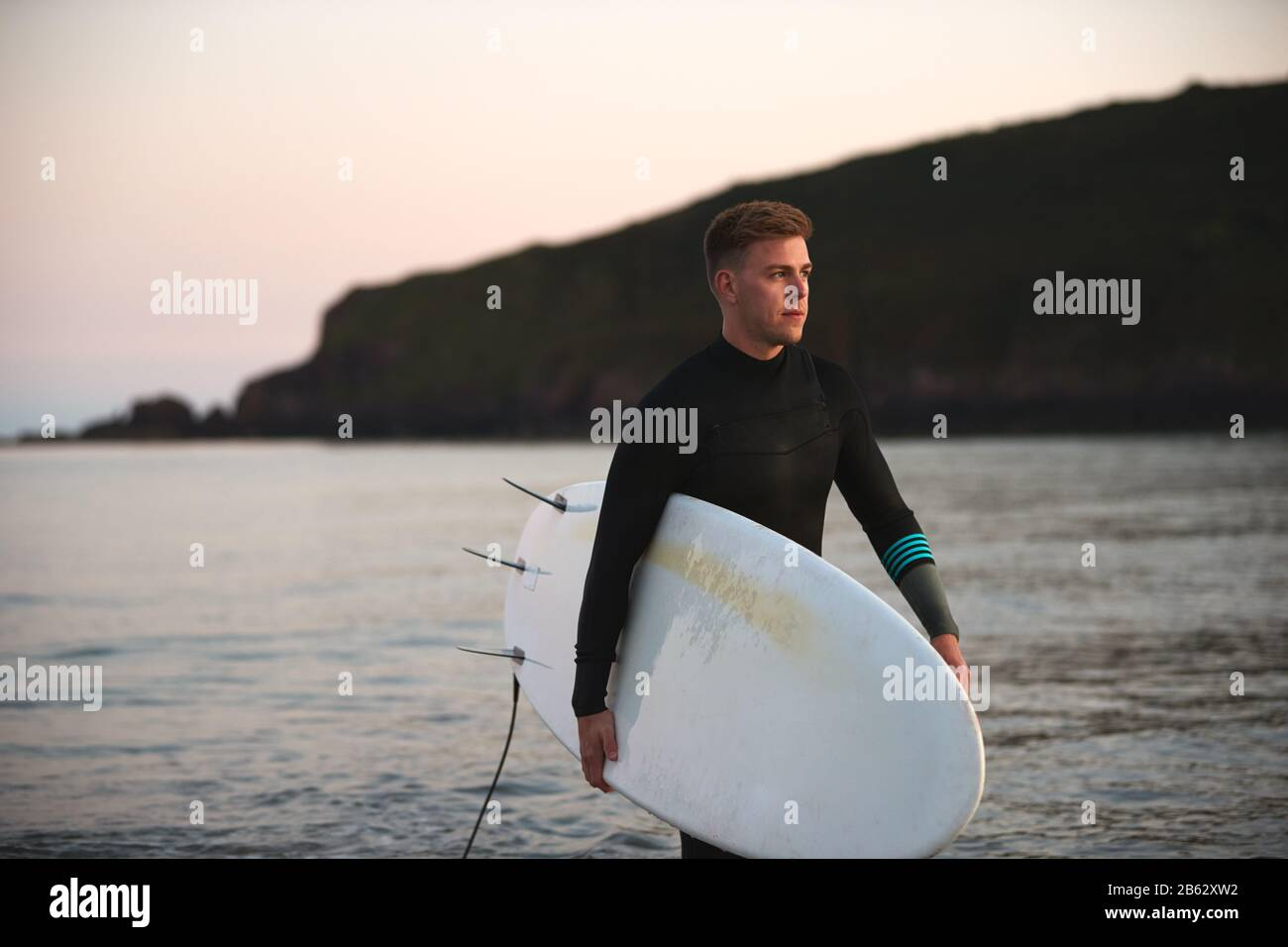 Man Wearing Wetsuit Carrying Surfboard As He Walks Out Of Sea Stock Photo