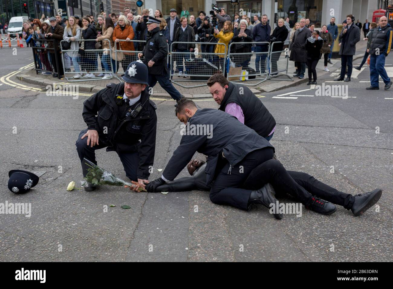 Pro-Democracy protesters with a Free Southern Cameroon group are tackled by Metropolitan police officers after dashing out from behind barriers outside Westminster Abbey during the Commonwealth Day service lead by the Queen and including members of the British royal family and Commonwealth ambassadors and dignitaries. They are holding placards saying Free President Ayuktabe Julius' (an Ambazonian separatist leader) and 'Justice for Babanki' (referring to allegations of soldier killings on villagers), on 9th March 2020, in London, England. At this, their last royal duty before stepping down for Stock Photo