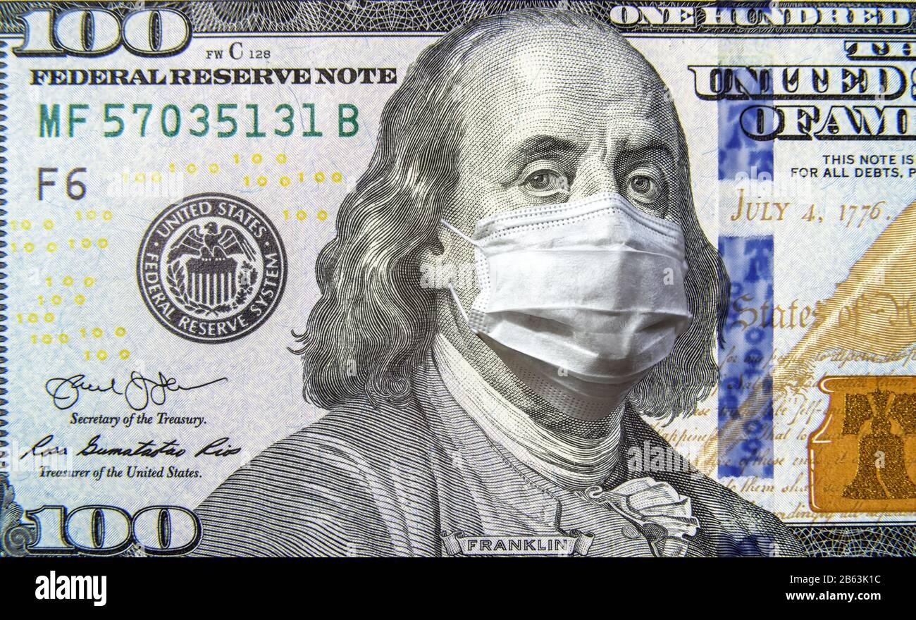 COVID-19 coronavirus in USA, 100 dollar money bill with face mask. Coronavirus affects global stock market. World economy hit by corona virus outbreak Stock Photo