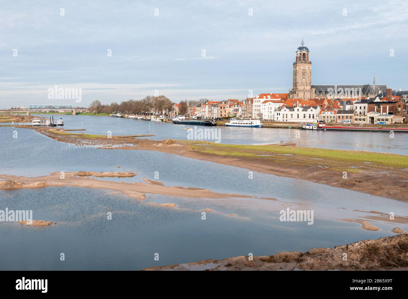 DEVENTER, THE NETHERLANDS - JANUARY 18, 2014: The historic center of Deventer with the Lebuinus Church and the river IJssel in the foreground. Stock Photo