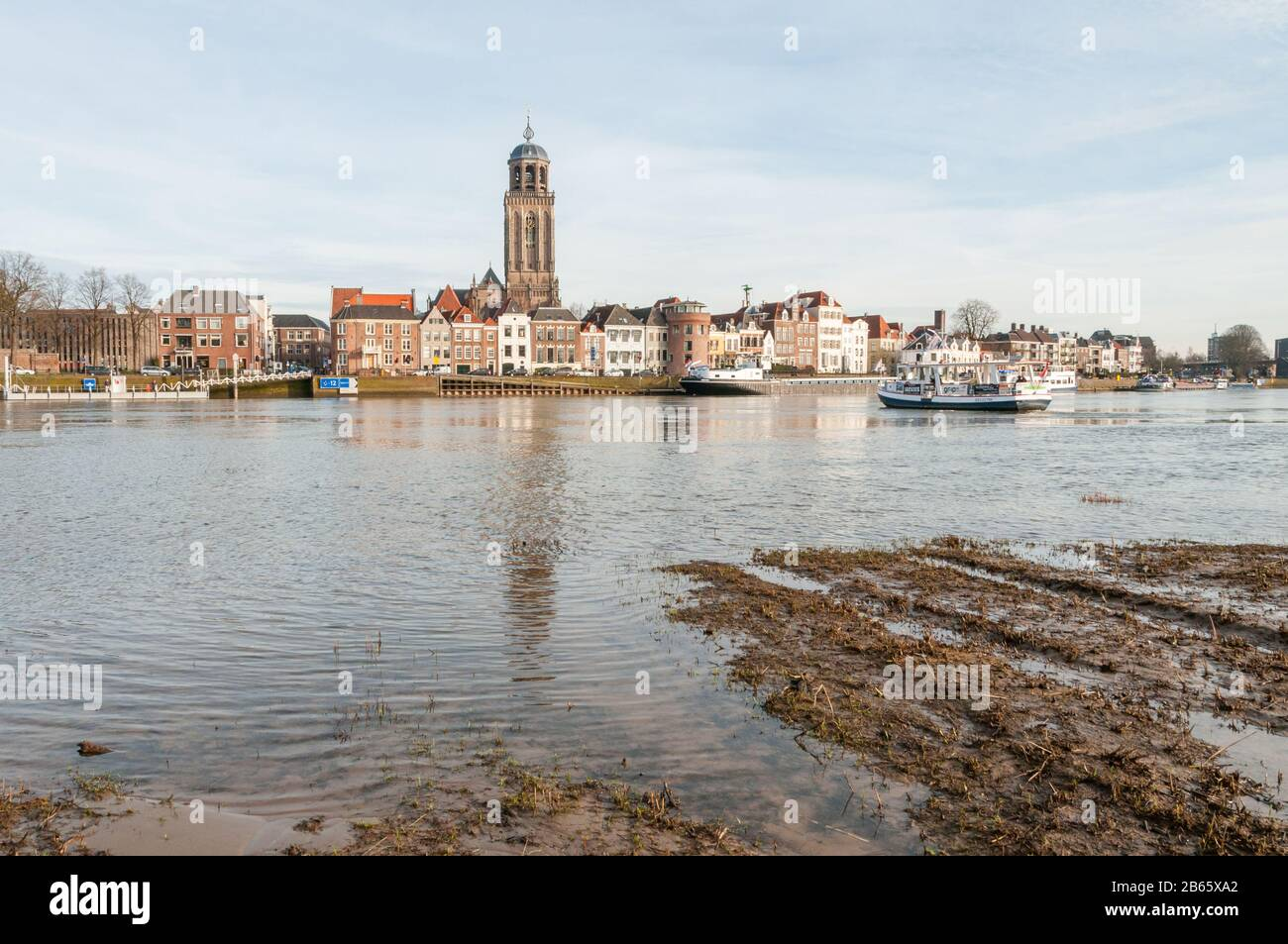 DEVENTER, THE NETHERLANDS - JANUARY 18, 2014: The historic center of Deventer with the Lebuinus Church and the river IJssel in the foreground. The fer Stock Photo