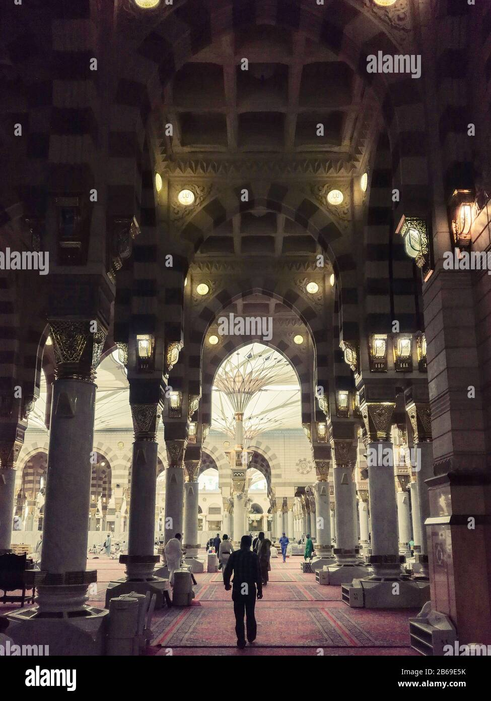Muslims worshiping after praying in Ramadan inside al-Masjid An-Nabawi which is the second most sacred mosque in Islam and one of three sacred ones Stock Photo