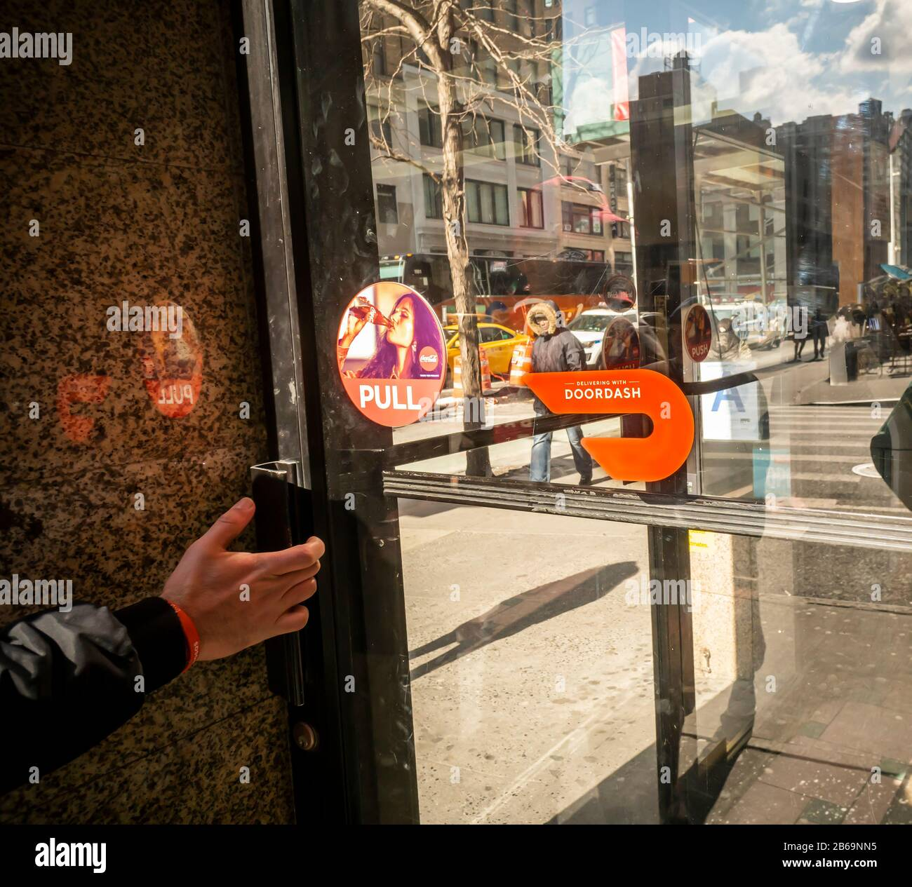 A sticker on the door of a delicatessen in New York informs shoppers of their use of Doordash as a delivery service, seen on Friday, February 28, 2020. (© Richard B. Levine) Stock Photo