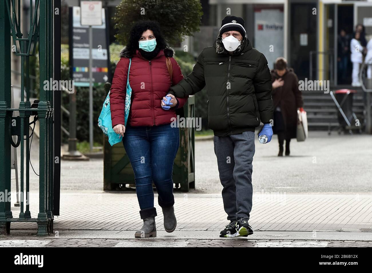 Turin, Italy. 09th Mar, 2020. TURIN, ITALY - March 09, 2020: Two people wearing protective masks and holding hands leave Molinette hospital. The Italian government imposed a virtual lockdown on the north of the country as part of measures to stop the spread of the coronavirus COVID-19 outbreak in Italy. (Photo by Nicolò Campo/Sipa USA) Credit: Sipa USA/Alamy Live News Stock Photo