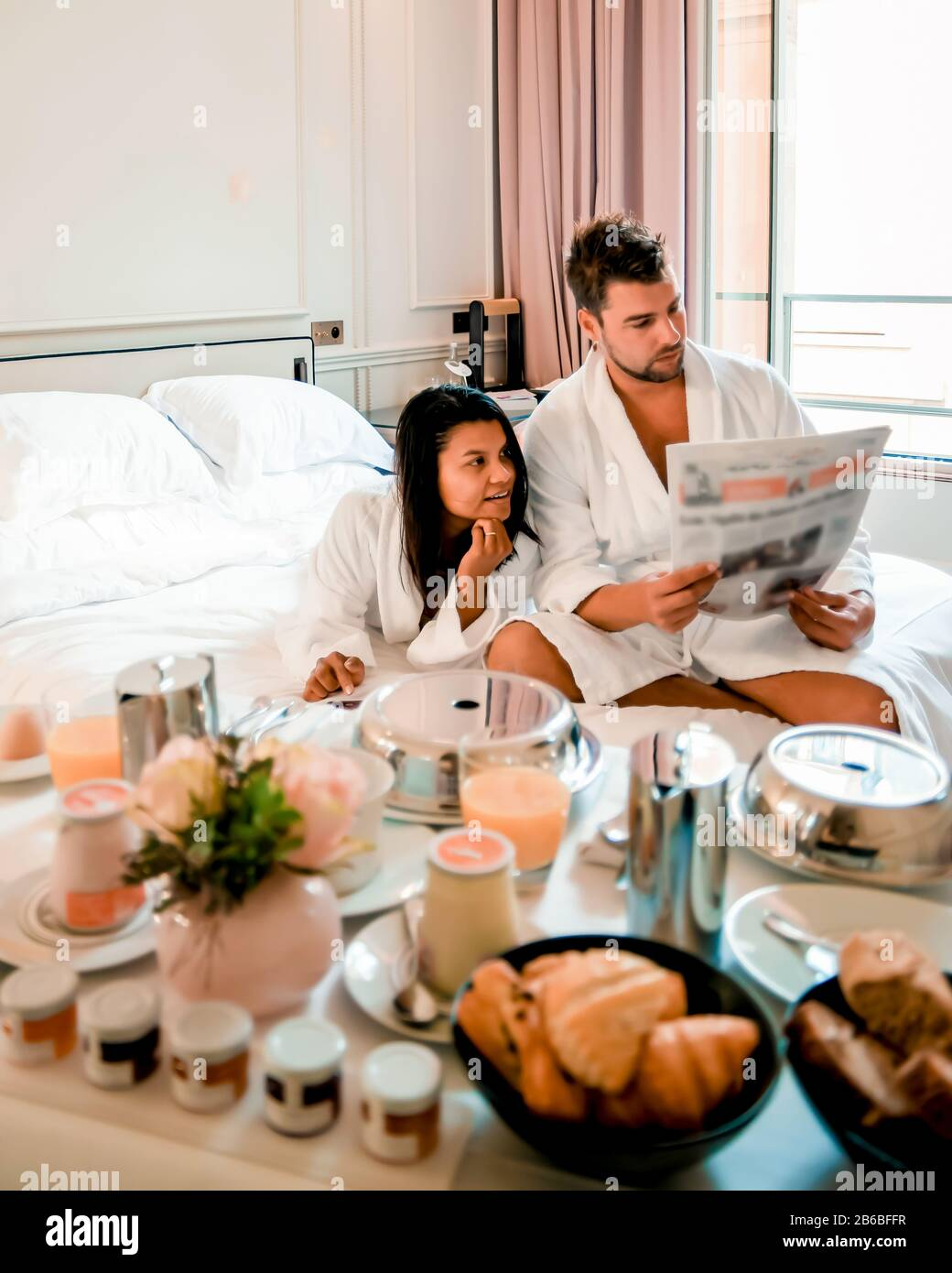 Morning wake up in bed in Paris with breakfast coffee and a newspaper, couple in bed men and woman honymoone valentine couple Stock Photo