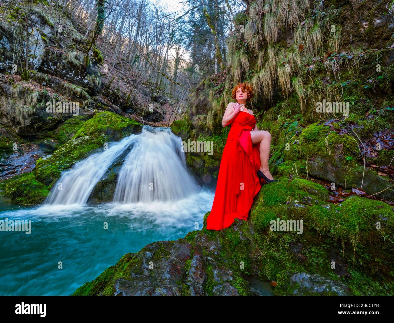 Fanciful woman wearing long Red dress legs heels in nature standing near flowing water waterfall Green forest Stock Photo