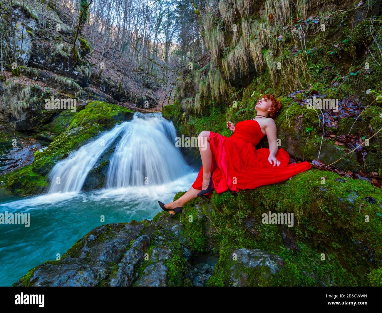 Fanciful woman wearing long Red dress legs heels in nature reclining near flowing water waterfall Green forest Stock Photo