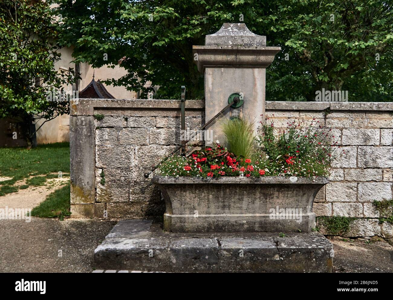 France, Ain departement, Auvergne - Rhone - Alpes région. The old stone water pump and its flowery trough on the church square in the Treffort medieval village hung on the first height of the Jura massif, Stock Photo
