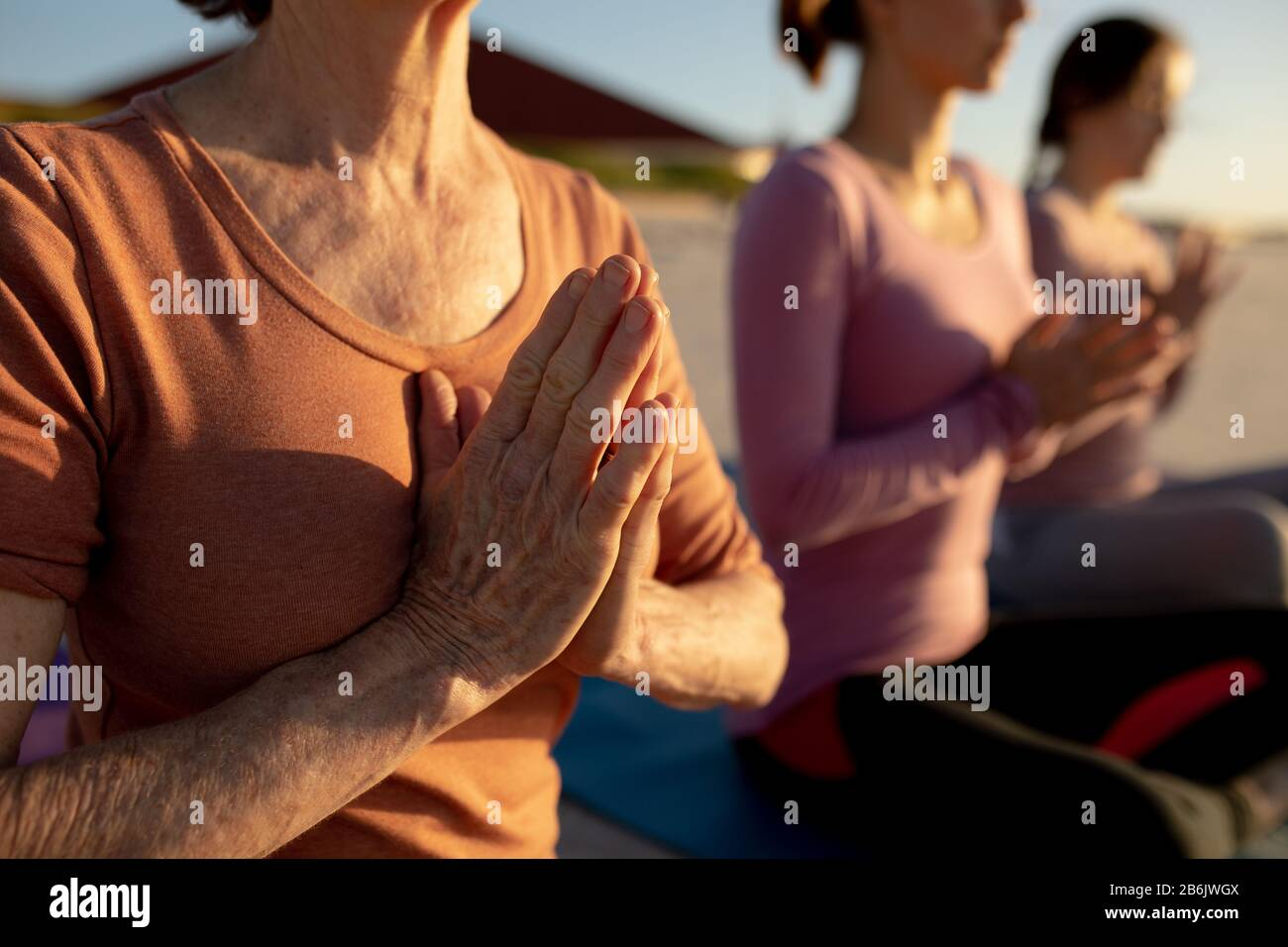 Close up view of women doing yoga at the beach Stock Photo