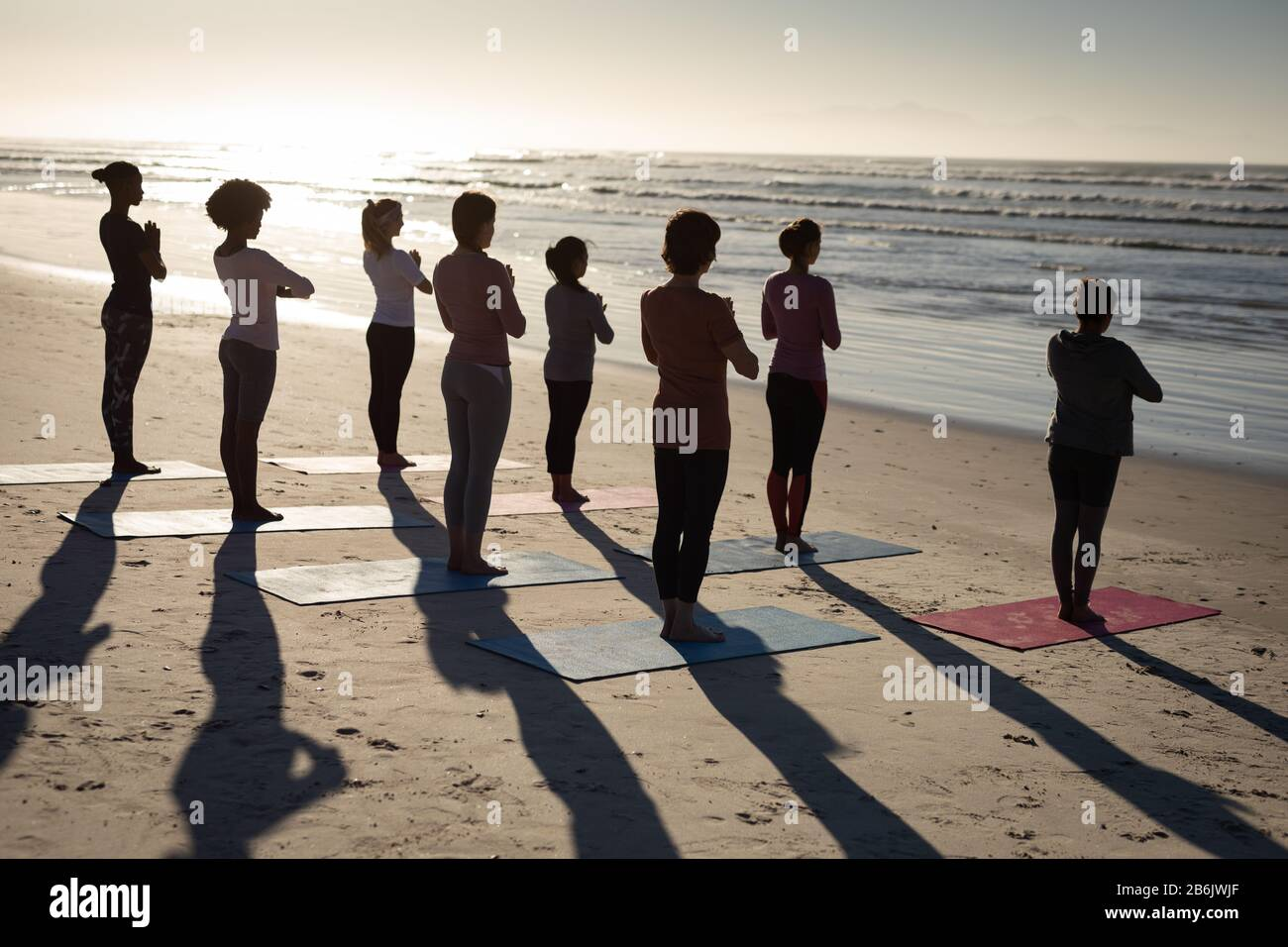 Rear view of women standing on yoga mats at the beach Stock Photo