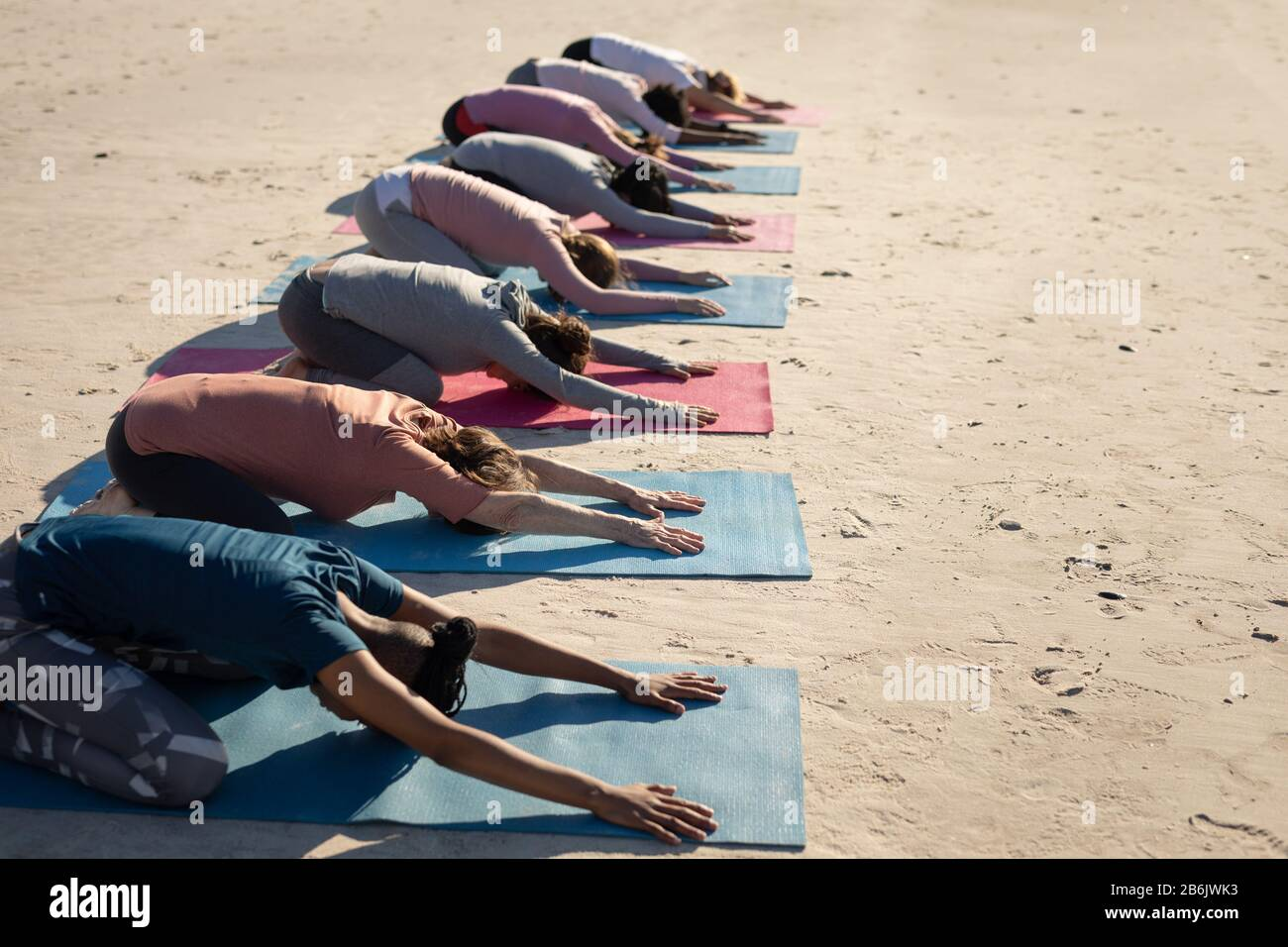 Side view of women aligned doing yoga together Stock Photo