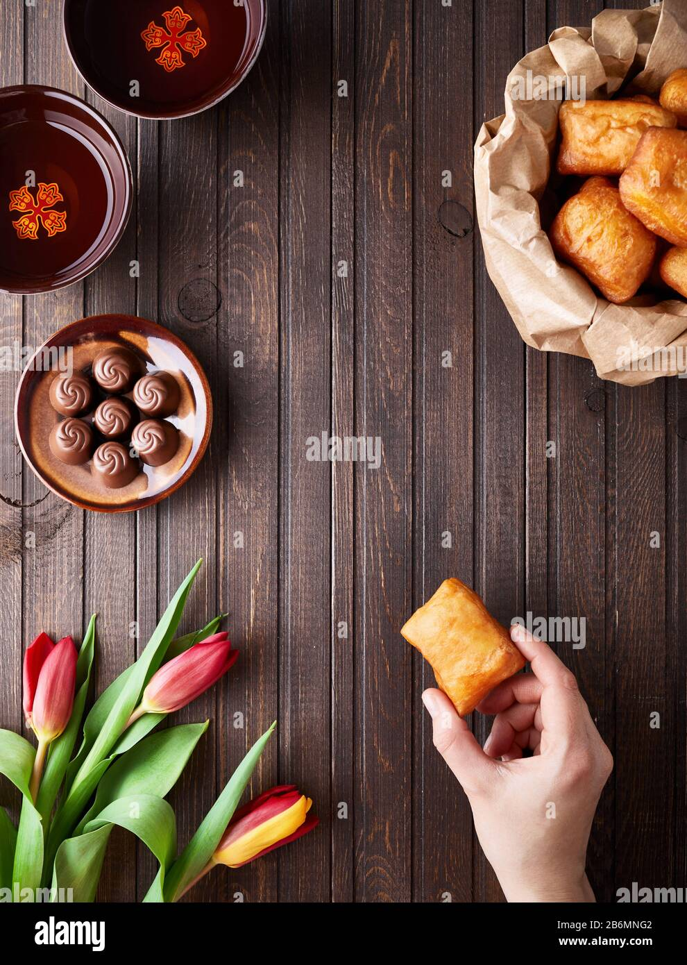 Kazakh national food and tulips during Nauryz festival on wooden brown background top view. Stock Photo