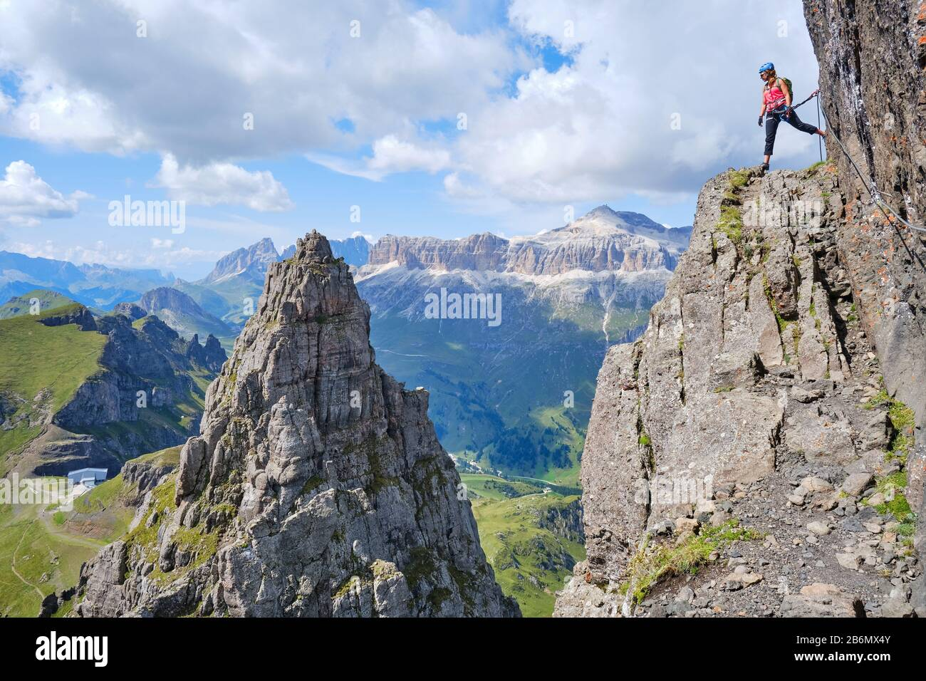 Woman on via ferrata Delle Trincee (meaning Way of the trenches), high above impressive pointy rock peak, with Sella group in the distance as backgrou Stock Photo