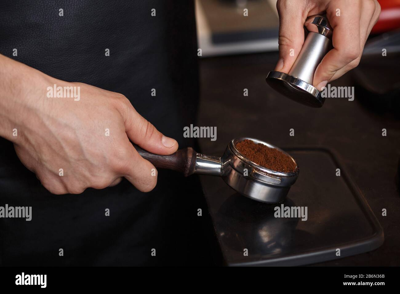 Young male barista pressing ground coffee into bottomless portafilter holder using tamper. Preparing espresso in professional coffee machine. Brewing Stock Photo