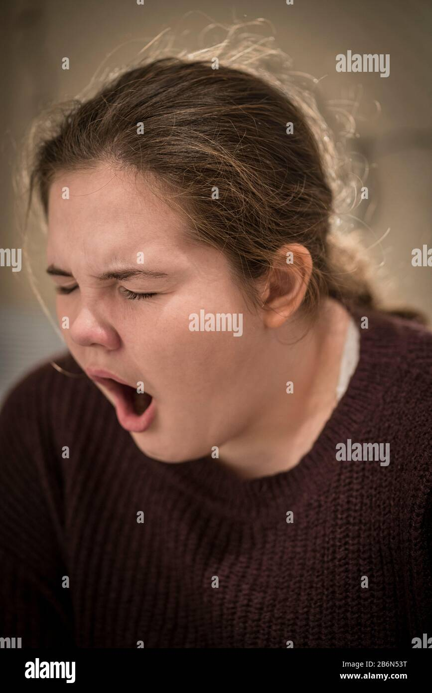 Face only, close up portrait of a 14 year old teenage girl yawning with her eyes closed Stock Photo