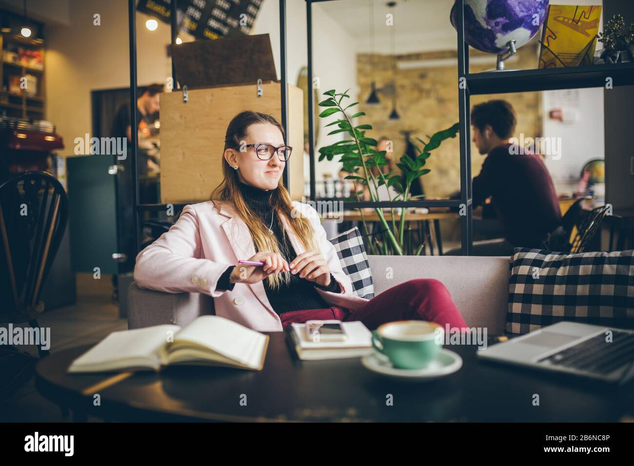 Beautiful Caucasian woman dreaming about something while sitting with computer in modern cafe. female freelancer thinking about new ideas during work Stock Photo