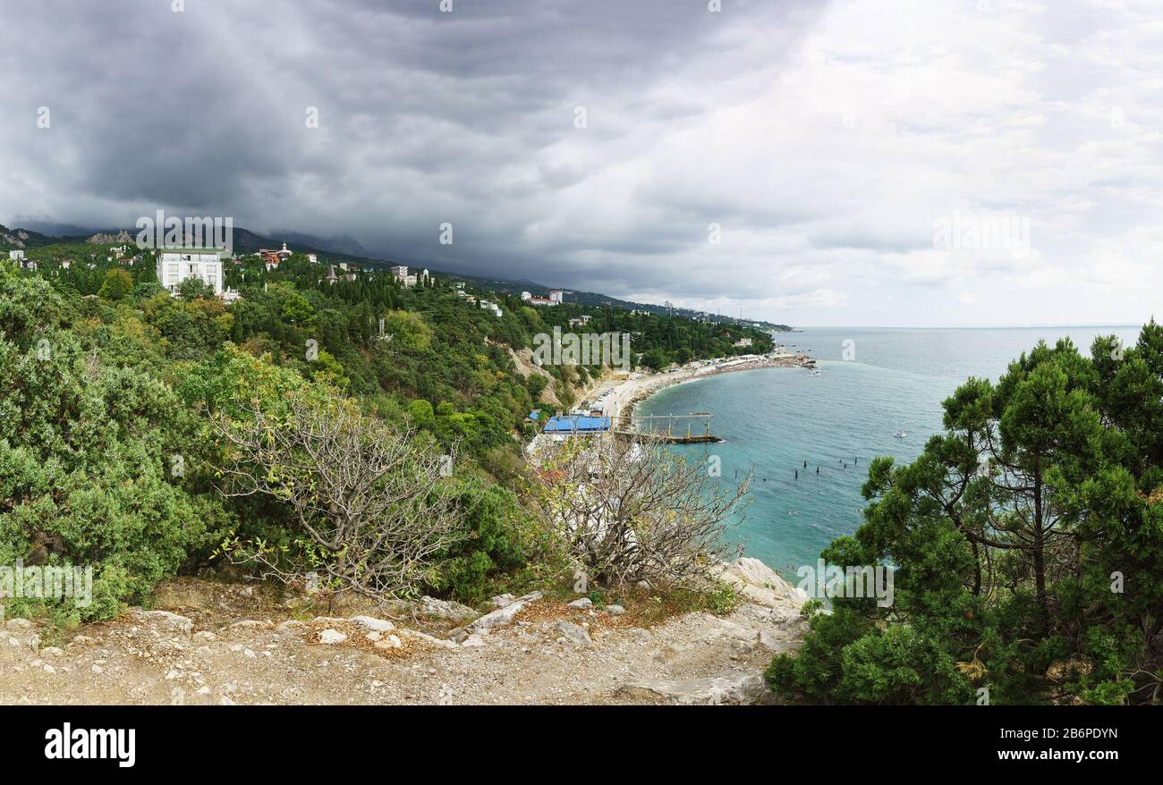 Rain cloud finds from the mountains to Simeiz village in Crimea. Cloudy day in the resort village Stock Photo