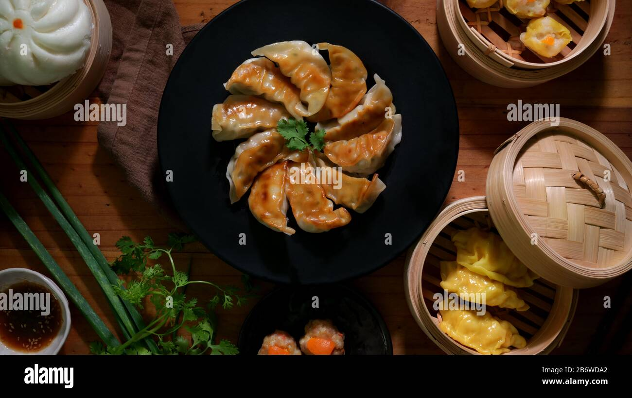Top View Of Dim Sum With Fried Japanese Gyoza Dumplings On Black Plate Chinese Dumplings And Bun Served On Traditional Steamer Stock Photo Alamy