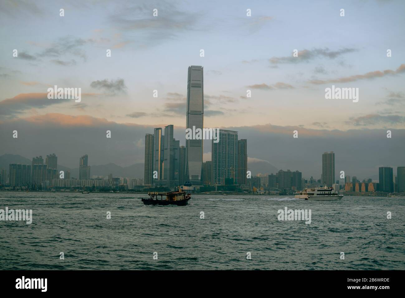 Hong Kong skyline at sunset with boats passing through the river Stock Photo