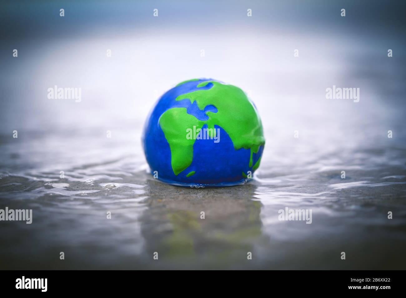 Erdkugel im Wasser, Symbolfoto fuer den Anstieg des Meeresspiegels durch den Klimawandel Stock Photo
