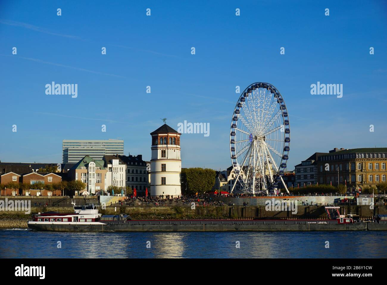 """View of """"Schlossturm"""" (castle tower) and Ferris Wheel across Rhine River. The castle tower once belonged to a castle that was destroyed in 1872. Stock Photo"""