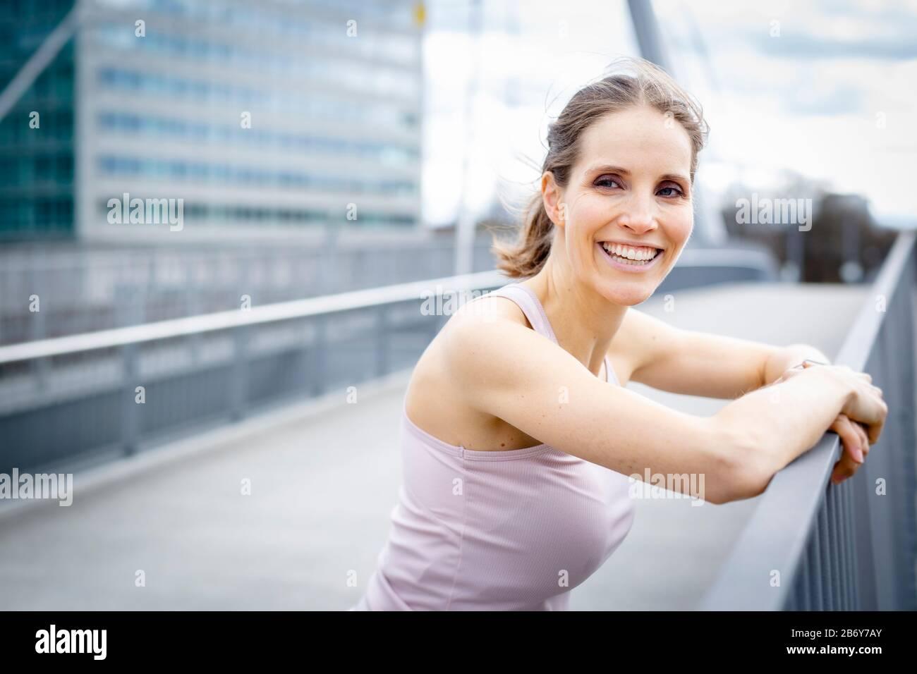 Happy young woman rests after jogging in the city and leans on a railing. Glückliche junge Frau ruht nach dem Joggen und stützt sich auf ein Geländer. Stock Photo