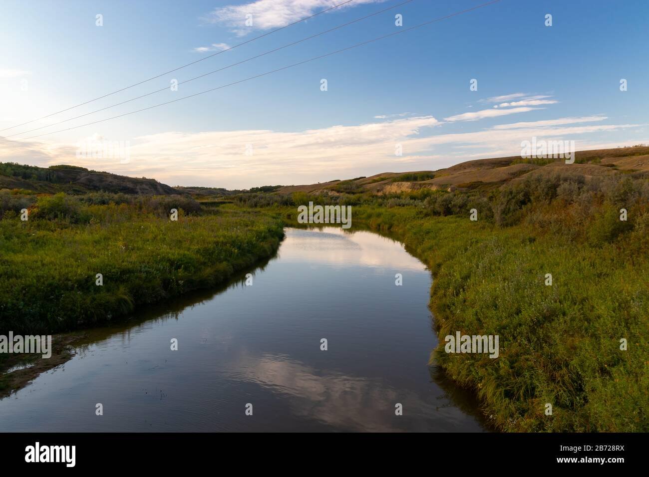 A calm and peaceful stream flowing through a valley in rural country side of the Saskatchewan Prairies in Canada with the sky reflecting in the water Stock Photo