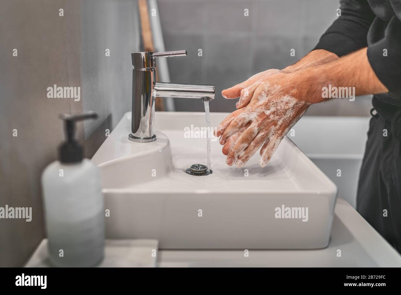 Washing hands with soap and hot water at home bathroom sink man cleansing hand hygiene for coronavirus outbreak prevention. Corona Virus pandemic protection by washing hands frequently. Stock Photo