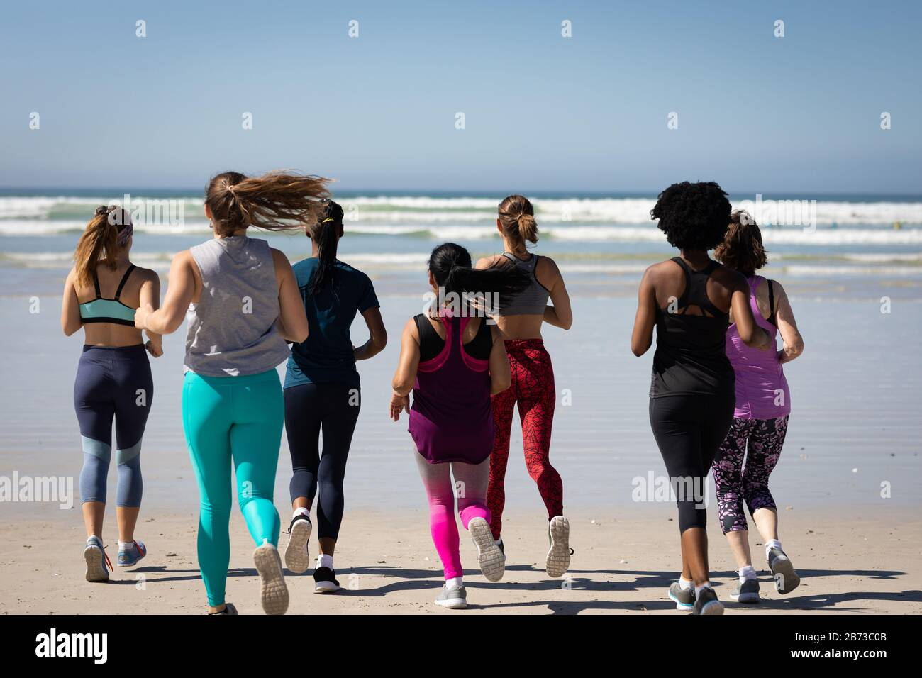 Rear view of women running at the beach Stock Photo