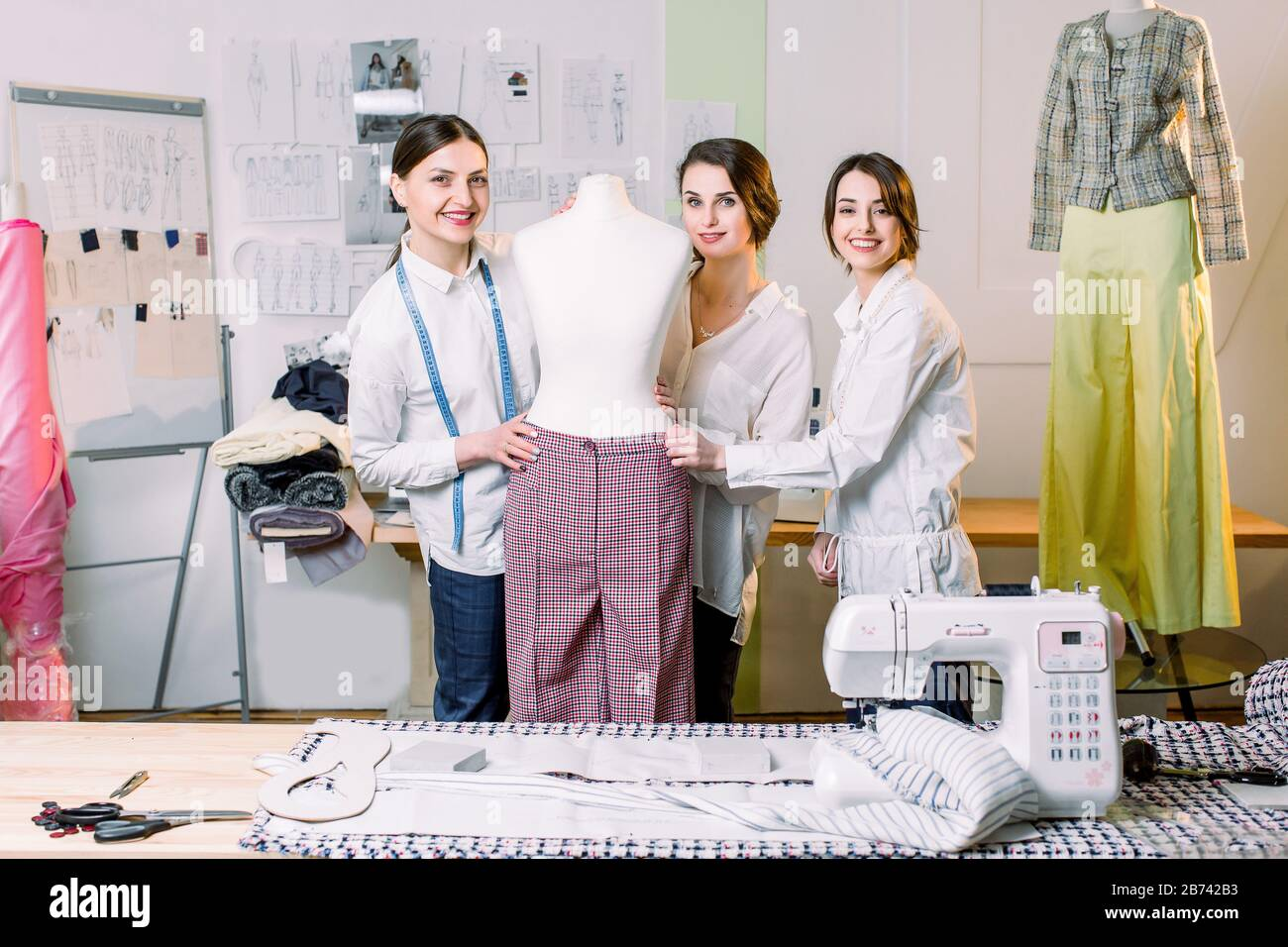 Three Happy Fashion Designers Working With Fabric Clothing Sketches Measuring Materials On Mannequin At The Studio Full Of Tailoring Tools And Equip Stock Photo Alamy
