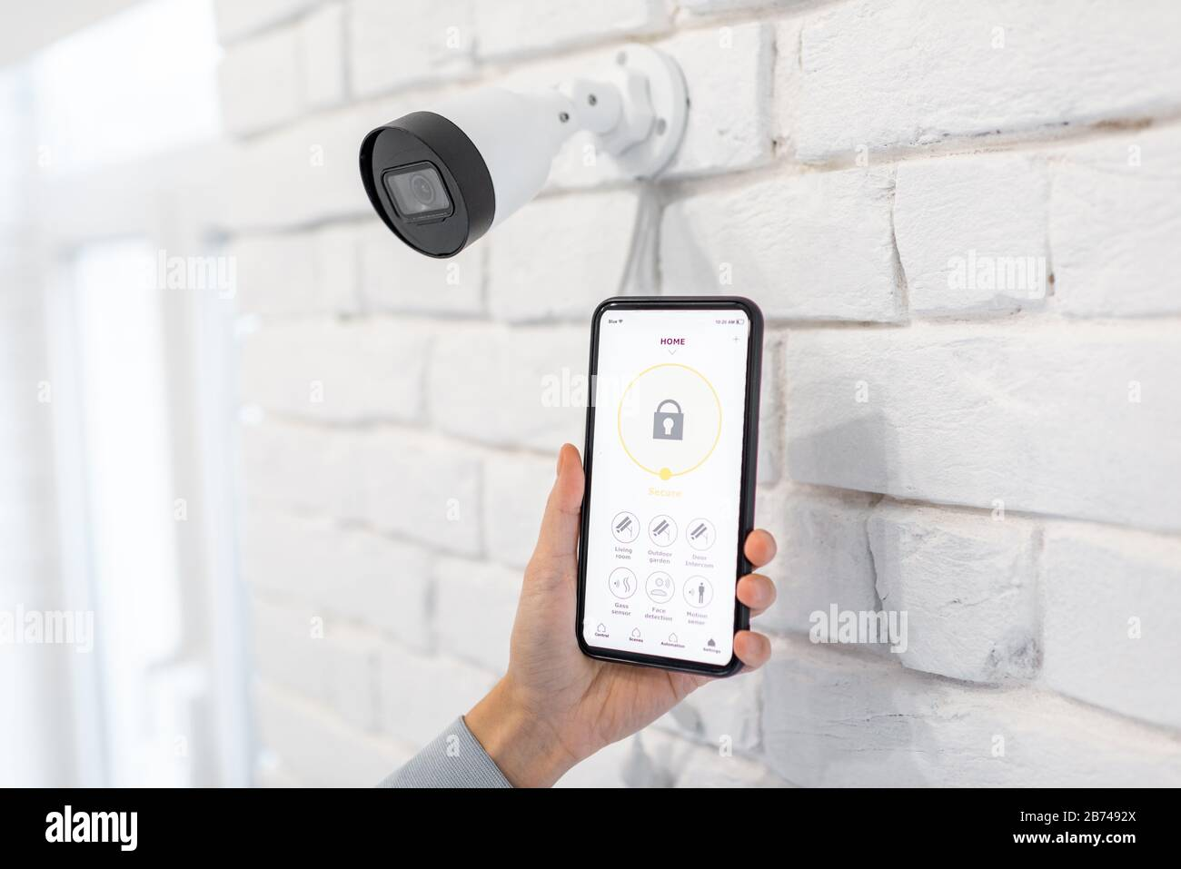 Controlling video surveillance and home alarm with mobile application, close-up on a smart phone with launched app. Concept of a wireless home security systems Stock Photo