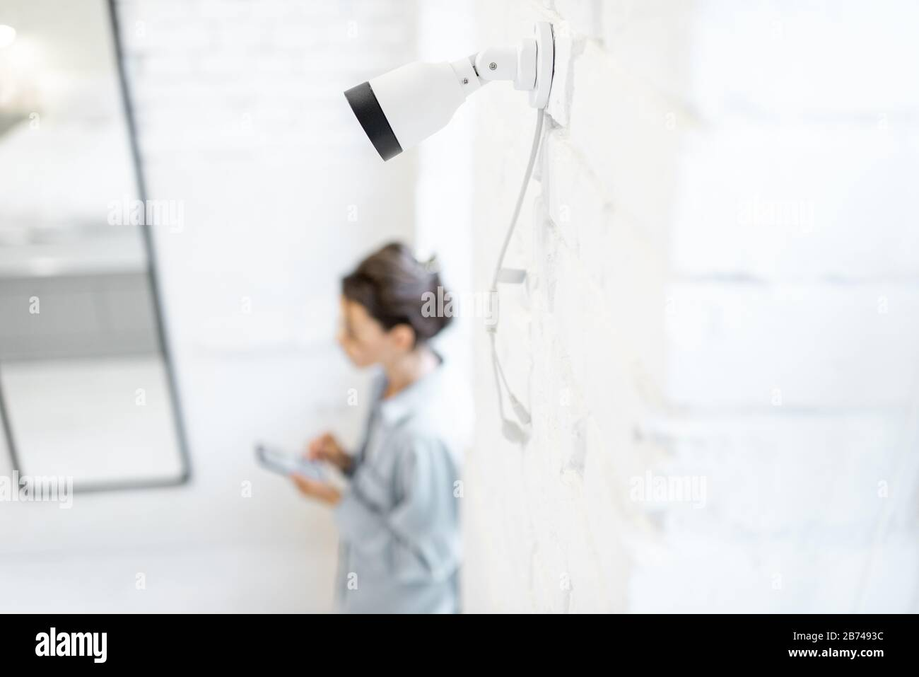 Woman controls home video surveillance with a smartphone indoors, view from the above and ip camera on the foreground. Concept of a wireless home security systems Stock Photo
