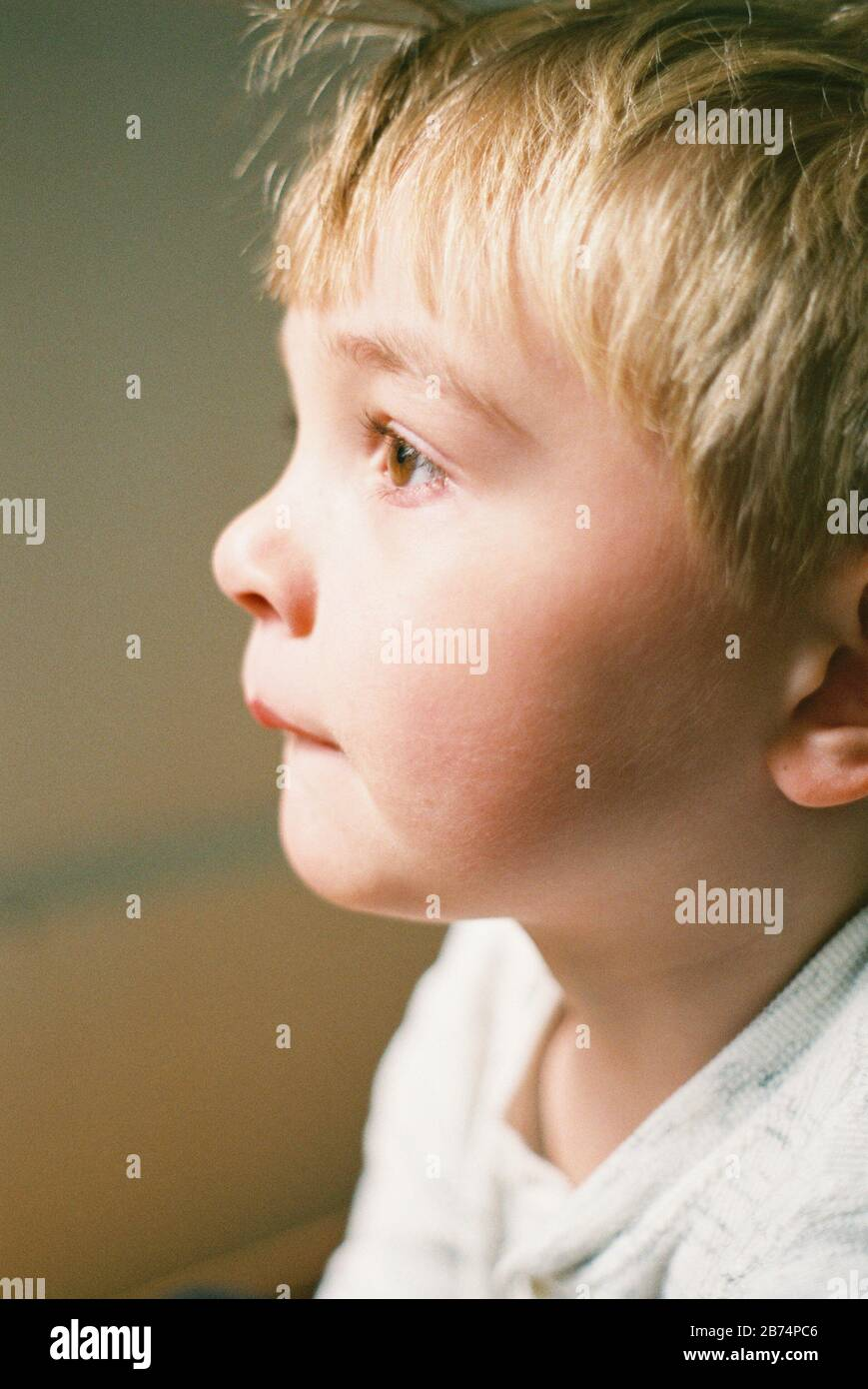 Little boy looking out the window, captured on film. Stock Photo