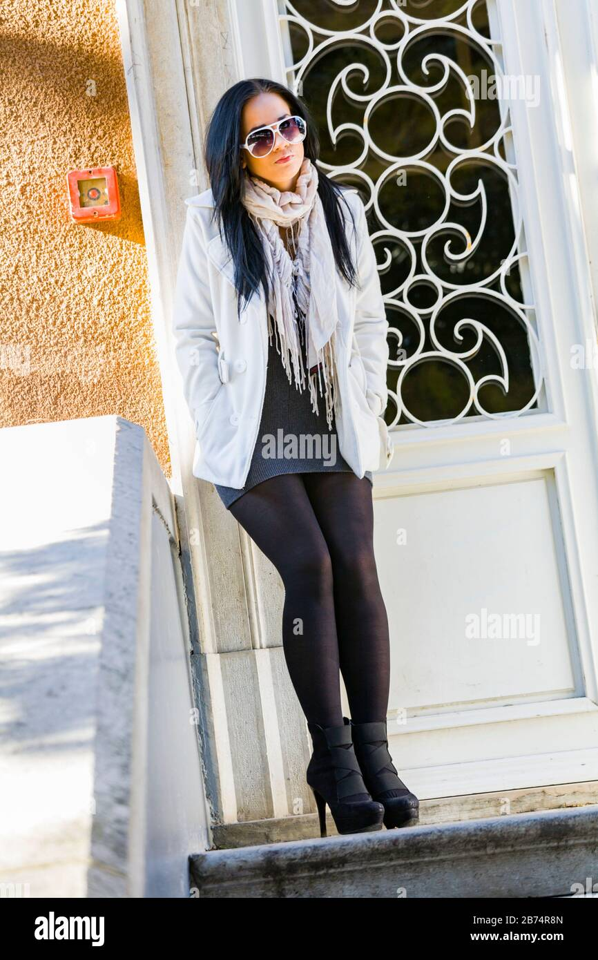 Teen girl serious looking at camera dark sunglasses glasses wearing Winter clothes stand porch entrance near doors door facing frontal view legs heels Stock Photo