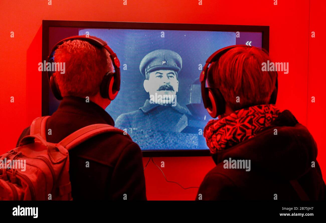 "Visitors of the exhibition ""The Red God - Stalin and the Germans"" watch a film about Stalin at the Hohenschoenhausen Memorial on 30.01.2018. The exhibition illustrates the personality cult around the Soviet dictator in the GDR and shows many objects of the Stalin cult. [automated translation] Stock Photo"