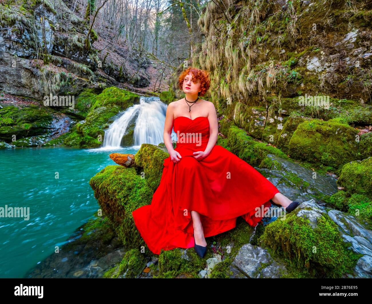 Fanciful woman wearing long Red dress legs heels in nature sitting spreading spread legs apart near flowing water waterfall Green forest Stock Photo