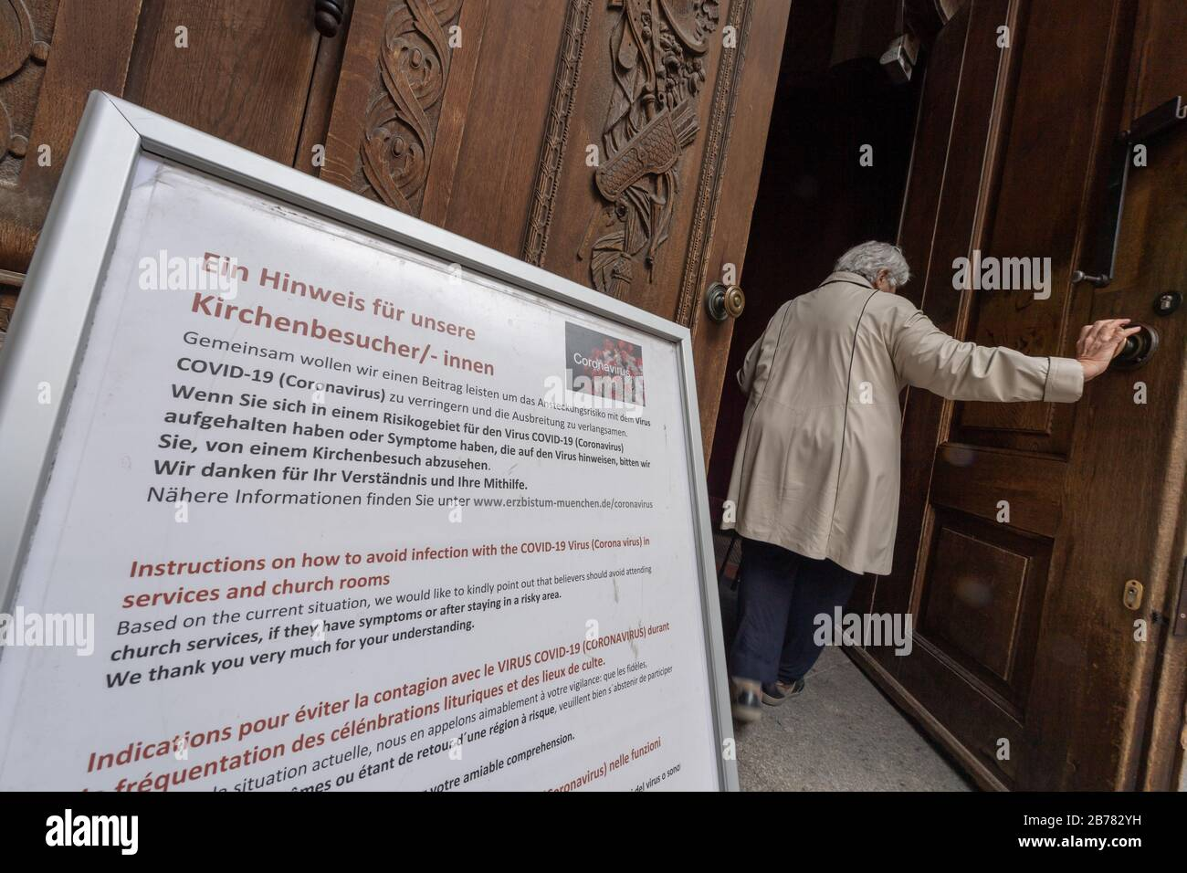 Munich, Germany. 14th Mar, 2020. A woman walks through the entrance door of the Frauenkirche, in front of which an operator advises visitors not to go to church because of the coronavirus. Credit: Peter Kneffel/dpa/Alamy Live News Stock Photo