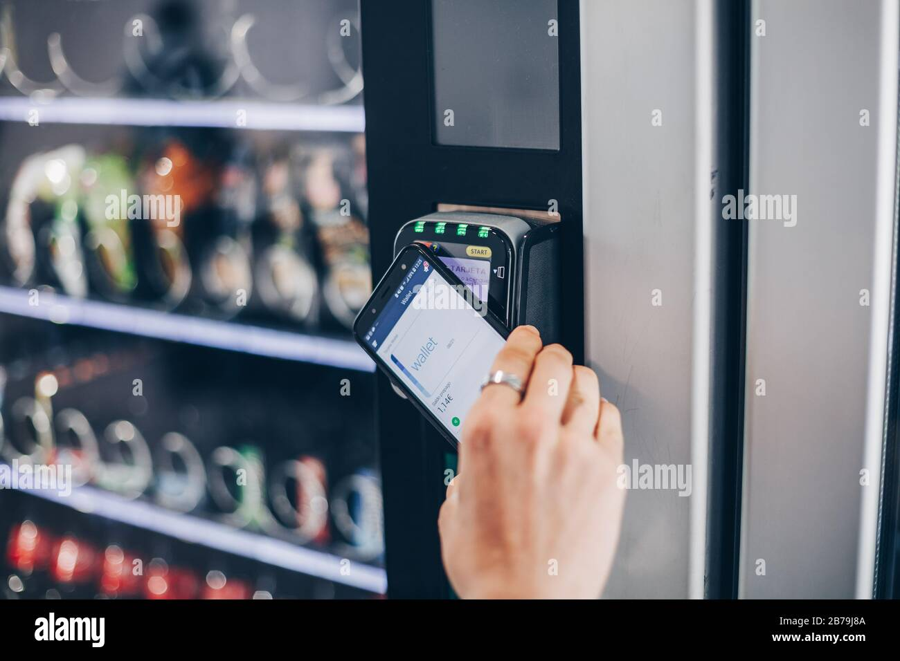 Student using the contactless payment method with mobile phone in a vending machine. Stock Photo