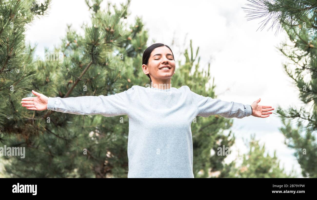 soul and body freedom. attractive woman with arms open and eyes closed meditating and understanding her being in nature Stock Photo