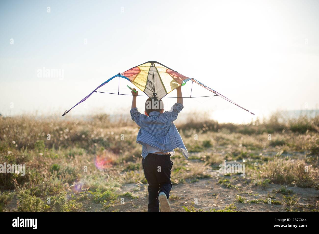 active little boy with color kite running towards bright sunset and sea shore trying to fly Stock Photo