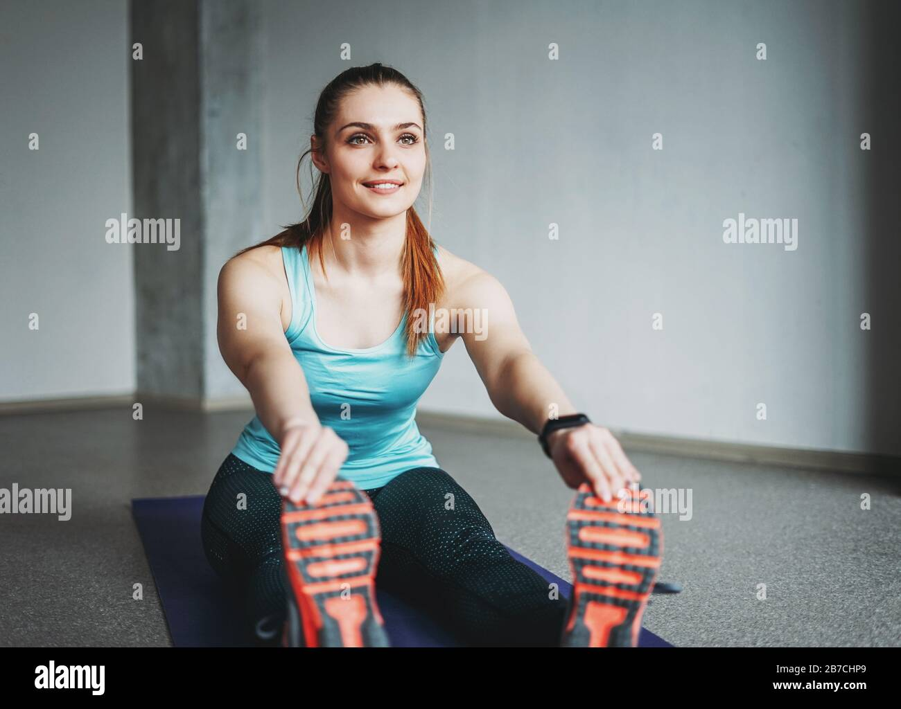 Attractive fit young woman sport wear fitness girl model doing stretching at the loft studio workout class Stock Photo