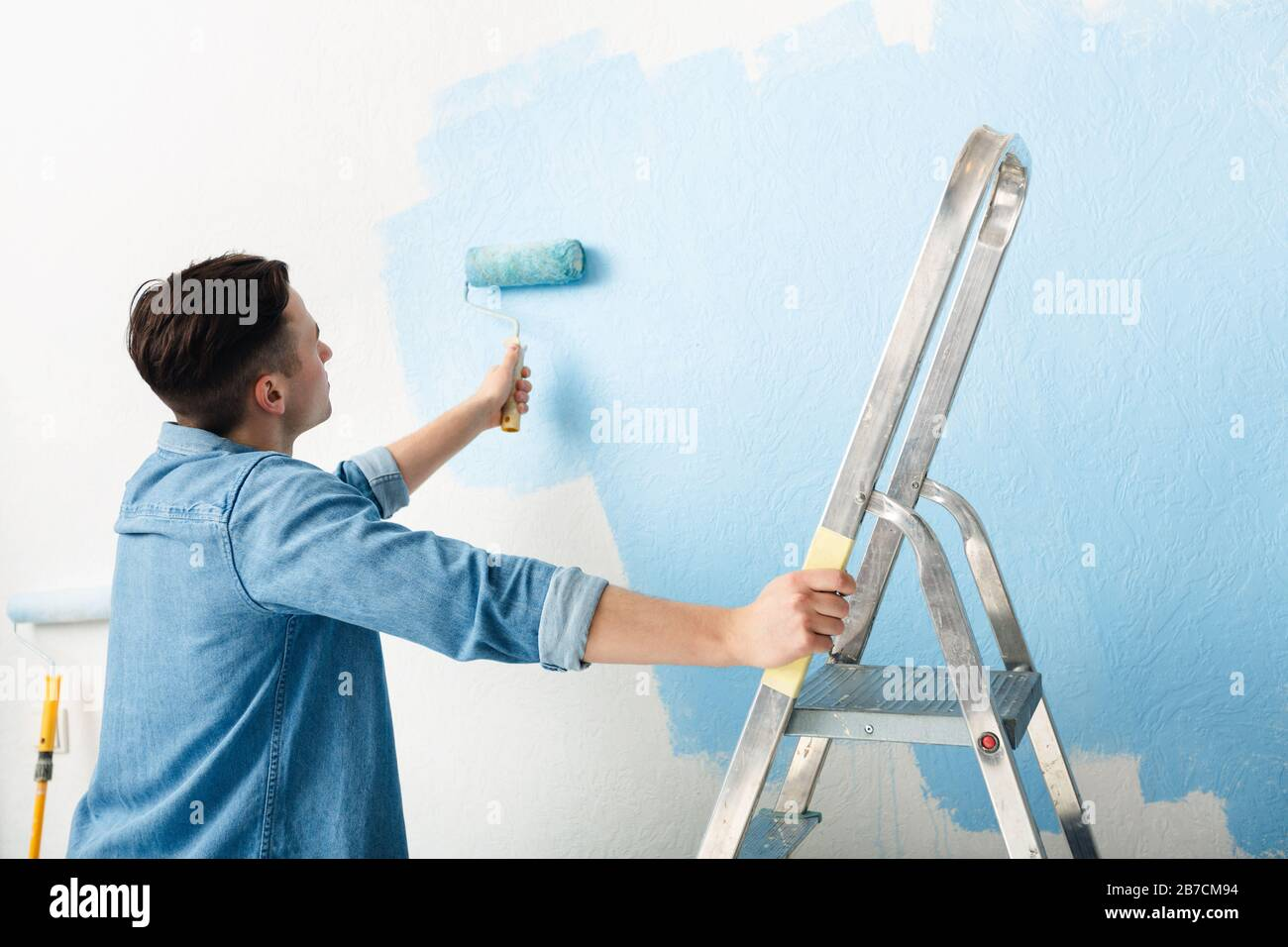 Young man leans on stepladder and paints wall Stock Photo
