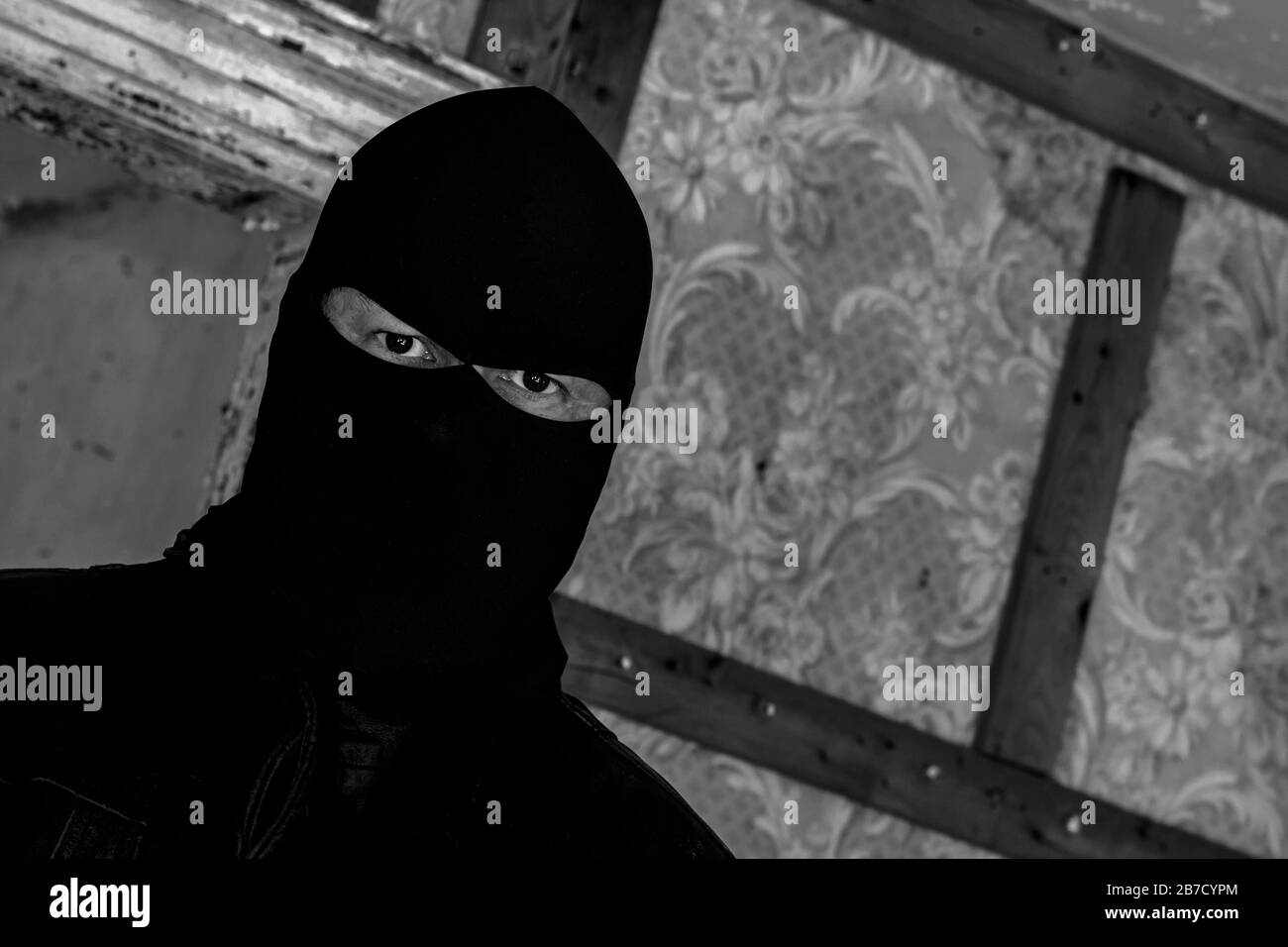 A Man Wearing A Mask Hood In An Abandoned Building He Is Staring At The Viewer Closeup View At An Angle Dark Black And White Image Stock Photo Alamy