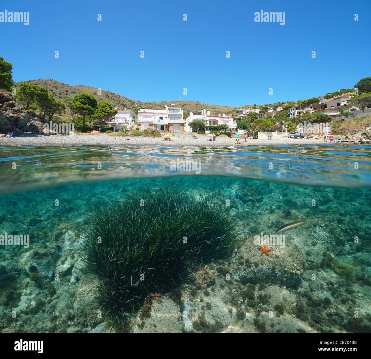 Spain Mediterranean sea summer vacations, beach coastline with buildings, split view over and under water surface, Costa Brava, Colera, Catalonia Stock Photo
