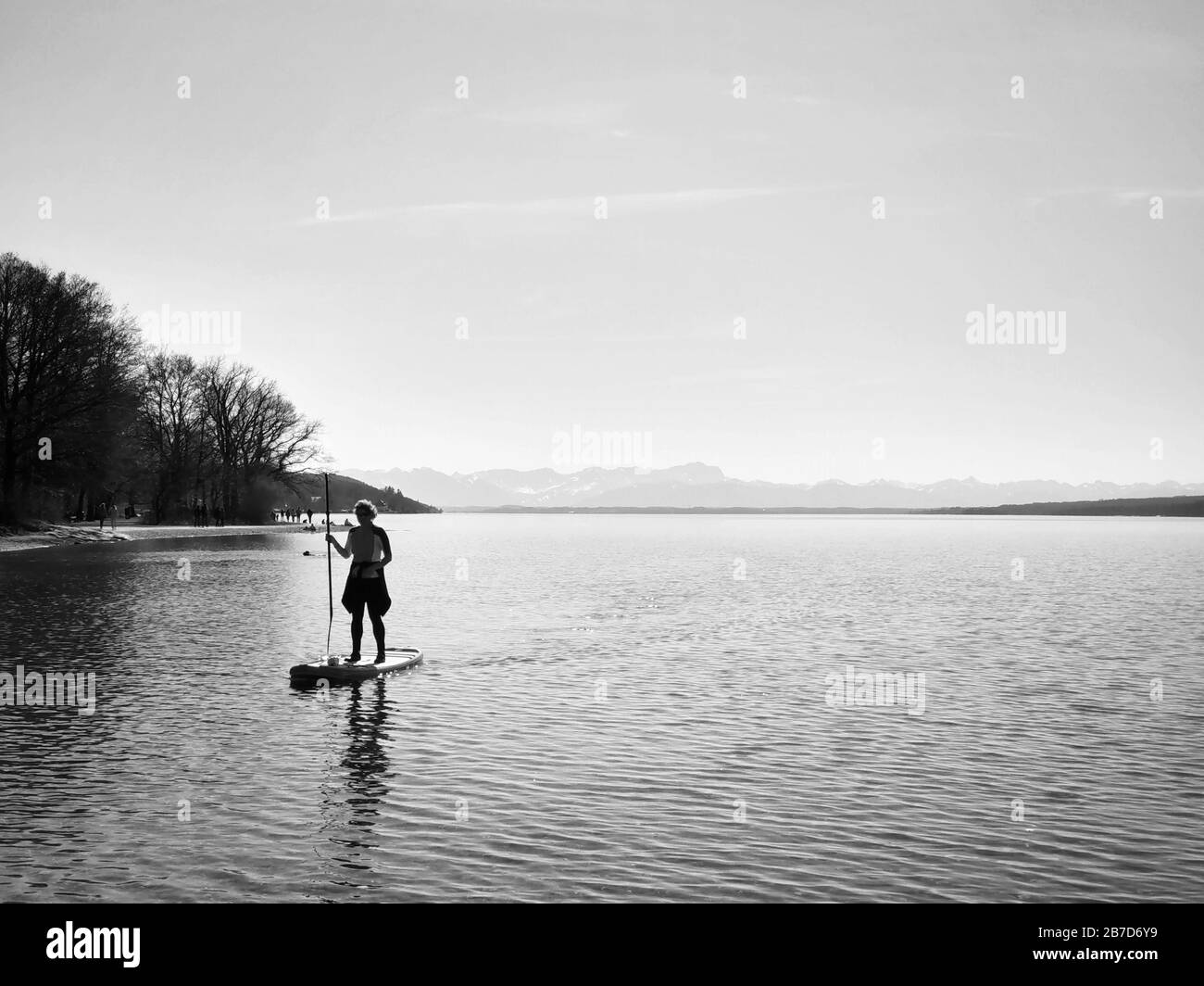 Starnberg, Bavaria, Germany. 15th Mar, 2020. A stand-up paddler on Lake Starnberg near Munich, Germany practices social distancing and flatten the curve during the European Coronavirus outbreak and subsequent measures taken to control the spread. Credit: Sachelle Babbar/ZUMA Wire/Alamy Live News Stock Photo