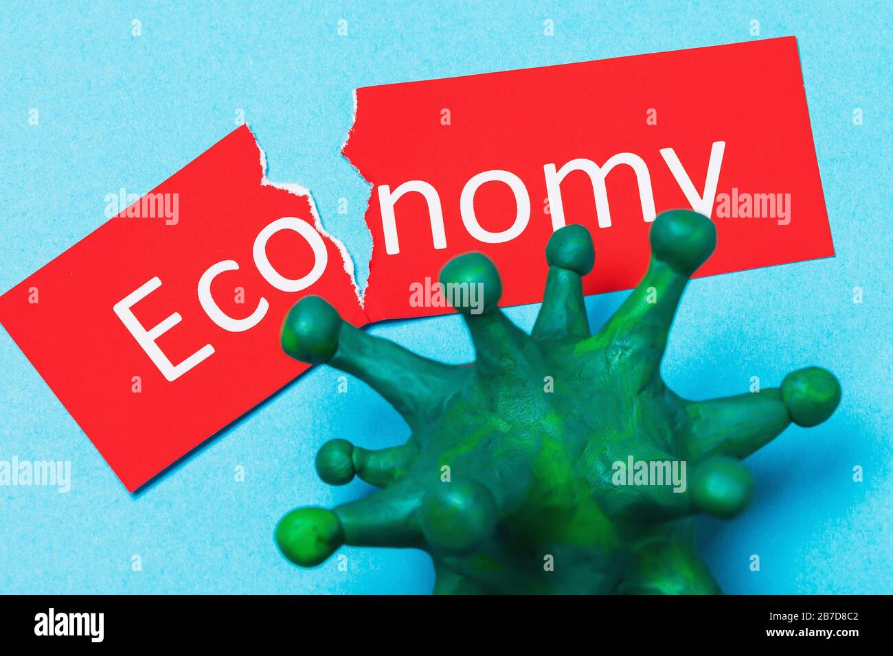 Torn tag with text and coronavirus. The concept of the impact of COVID-19 on the economy Stock Photo
