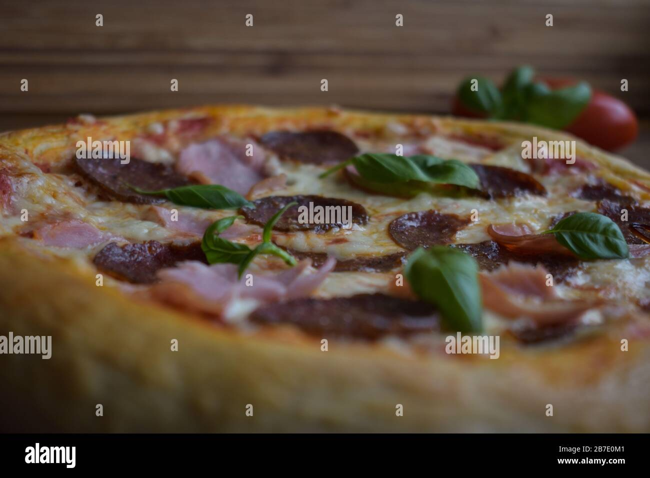 Homemade Pizza Baked In Oven On Pizza Stone With Peperoni And Ham Garnished With Basil Stock Photo Alamy