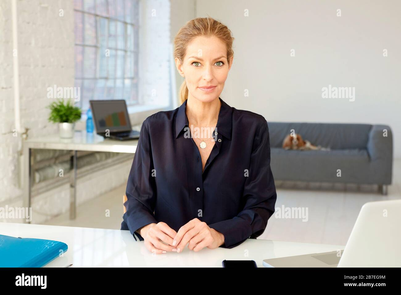 Portrait shot attractive middle aged businesswoman looking at camera and smiling while sitting at office desk. Stock Photo
