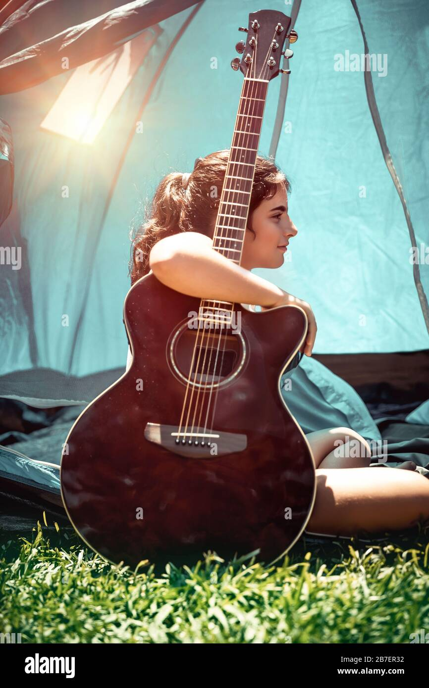 Teen girl with pleasure spending holidays in summer camp, pretty child sitting with a guitar near the tent, singing song and having fun Stock Photo